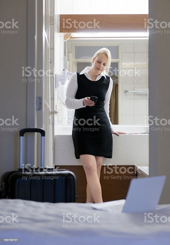 businesswoman in hotel bathroom looking at smart phone stock photo