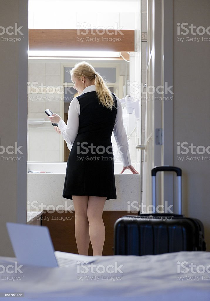 businesswoman in hotel bathroom looking at smartphone stock photo