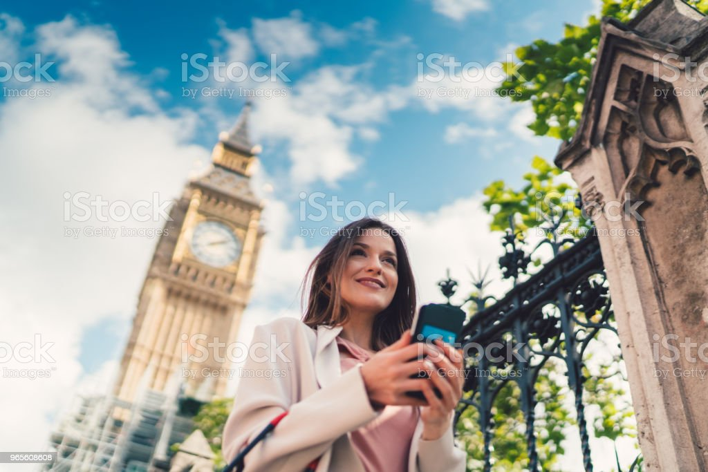 Businesswoman in London hailing a taxi via mobile app on smartphone stock photo