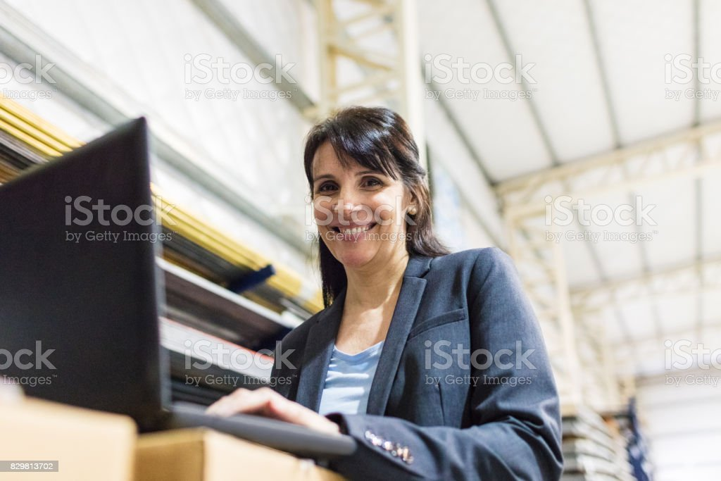 Businesswoman in manufacturing plant with laptop royalty-free stock photo