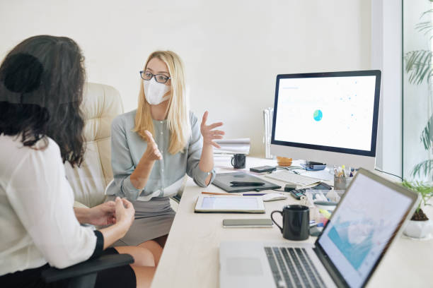 Businesswoman in medical mask explaining her idea stock photo