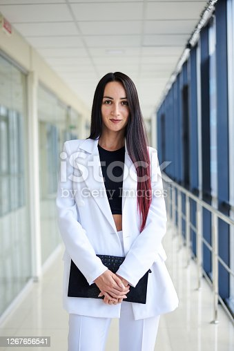 Young brunette woman, wearing white pants and jacket, standing in light passageway with huge windows, holding black clutch purse, posing for social media. Businesswoman on a break. Female portrait.