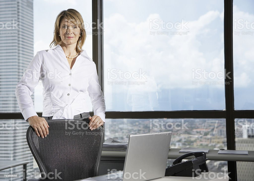 Businesswoman in office by large windows looking at camera stock photo