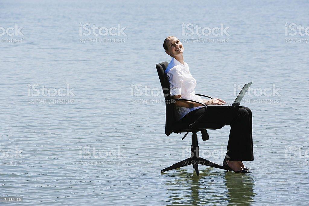Mulher de Negócios no escritório cadeiras na água com computador portátil a sorrir foto de stock royalty-free