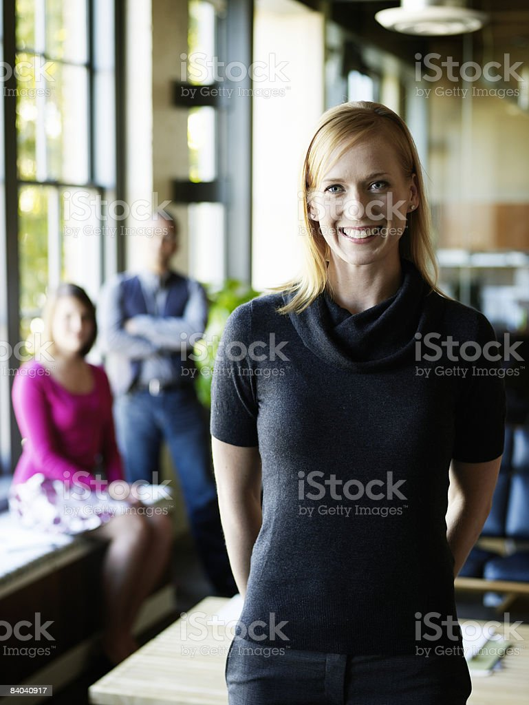 Businesswoman in office, colleagues in background foto stock royalty-free