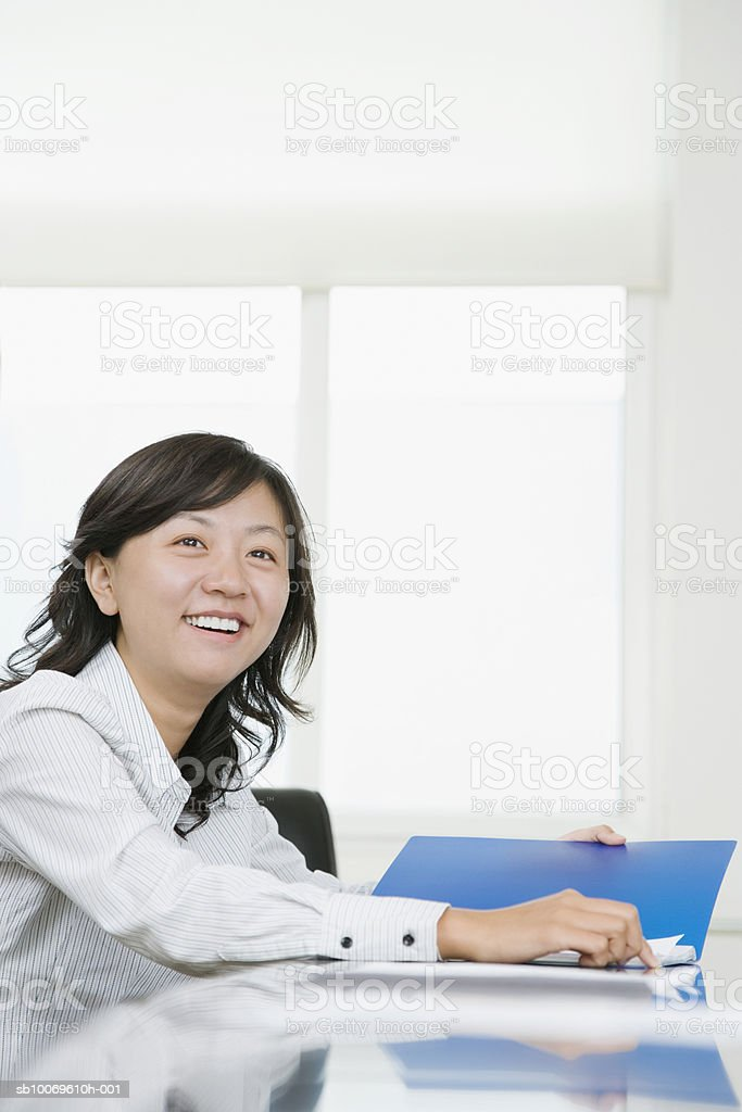 Businesswoman in office holding documents, smiling royalty-free stock photo