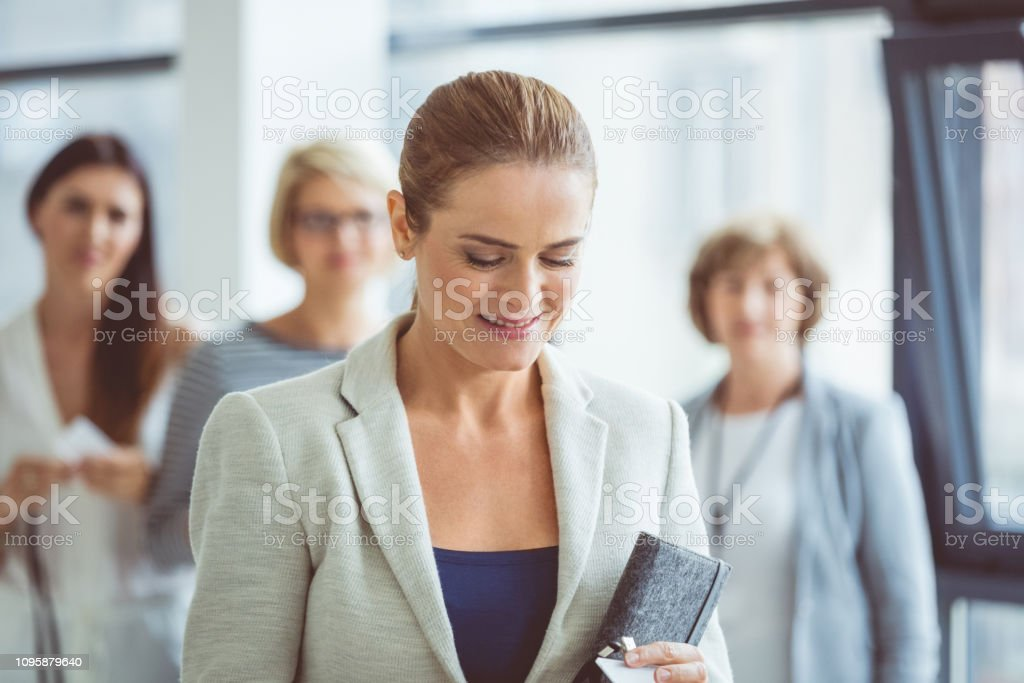 Businesswoman in office lobby Businesswoman standing in the office lobby with colleagues in background during a break in seminar. Adult Stock Photo