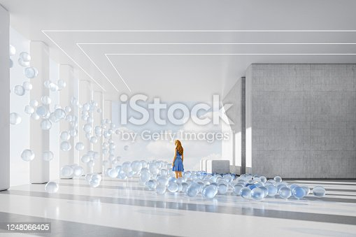 Businesswoman in office lobby with bouncing abstract glass spheres. 3D generated image.