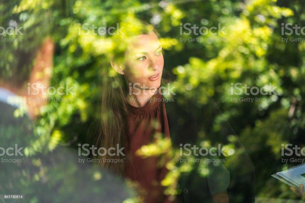 Geschäftsfrau im Büro durch Glas gesehen – Foto