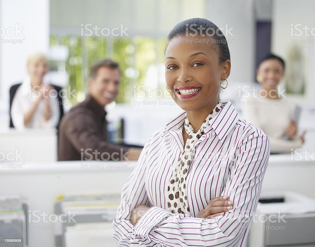 Businesswoman in office with three co-workers in background 免版稅 stock photo