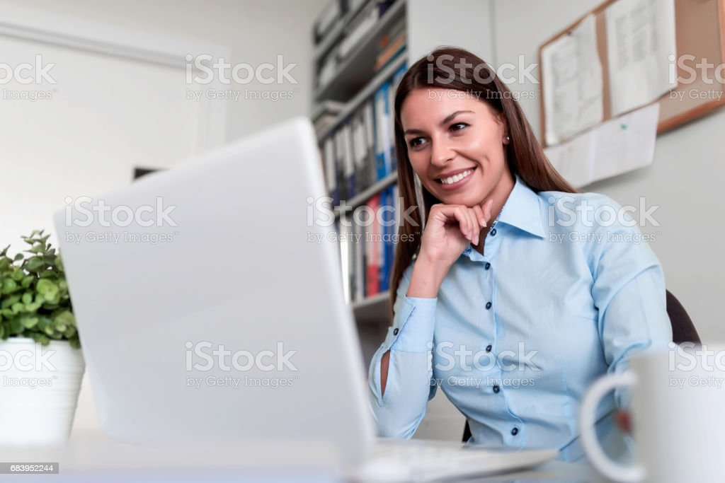 Businesswoman in office working on laptop computer stock photo