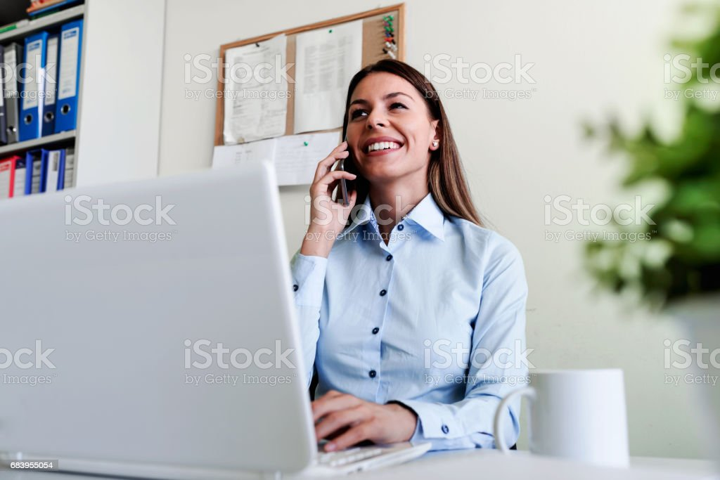 Businesswoman in office working on laptop talking over phone stock photo