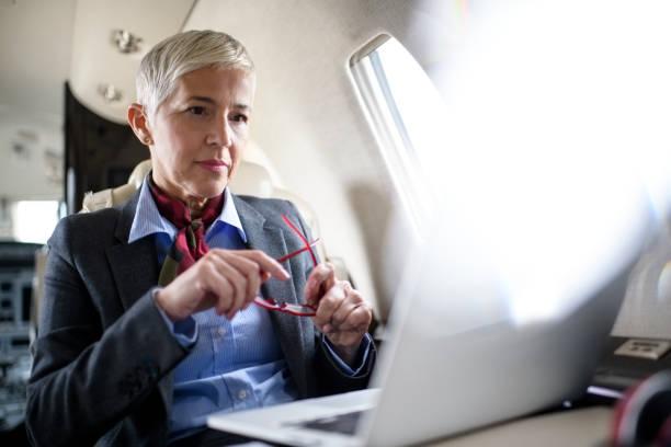 businesswoman in private jet airplane - senior business woman tablet imagens e fotografias de stock