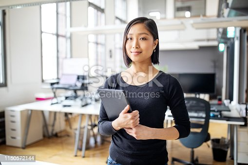 Portrait of confident young female professional at office with digital tablet. Businesswoman in smart casuals standing in office.