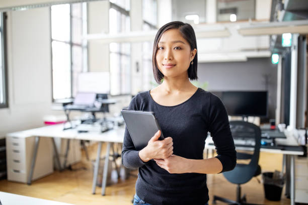 Businesswoman in smart casuals standing in office Portrait of confident young female professional at office with digital tablet. Businesswoman in smart casuals standing in office. only japanese stock pictures, royalty-free photos & images
