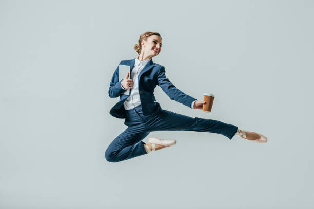 businesswoman in suit and ballet shoes jumping with coffee and digital tablet stock photo