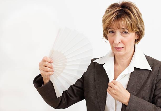 businesswoman in suit fanning herself with a paper fan - mature woman fever on white bildbanksfoton och bilder