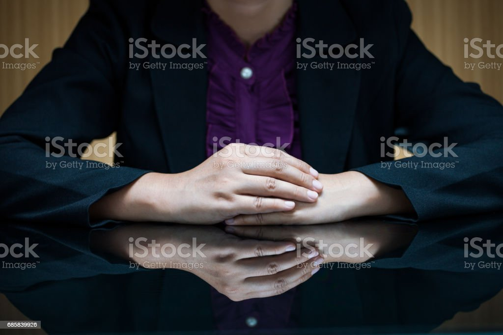 Businesswoman in suit sitting at a desk and clasp her hand stock photo