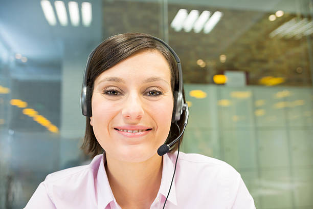 Businesswoman in the office on videoconference with headset, Sky stock photo