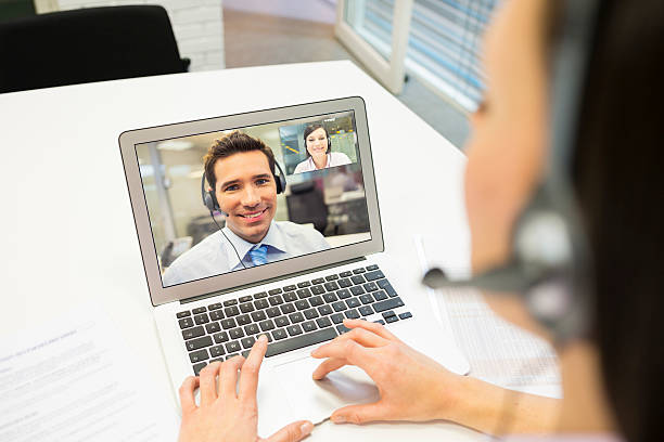 Businesswoman in the office on videoconference with headset, Skype stock photo