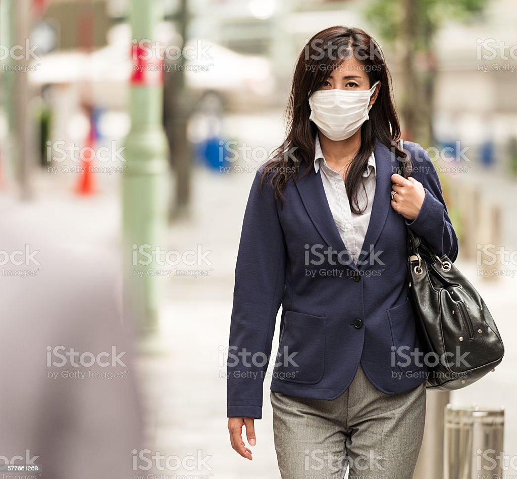 Businesswoman in Tokyo wearing protective face-mask stock photo