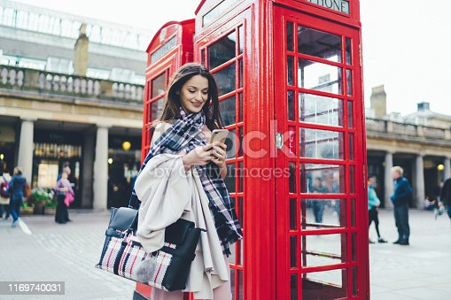 Smiling woman standing near red telephone booth using phone