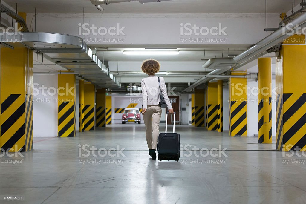 Businesswoman in underground garage Back view of businesswoman walking on the underground parking and carrying suitcase. 2015 Stock Photo