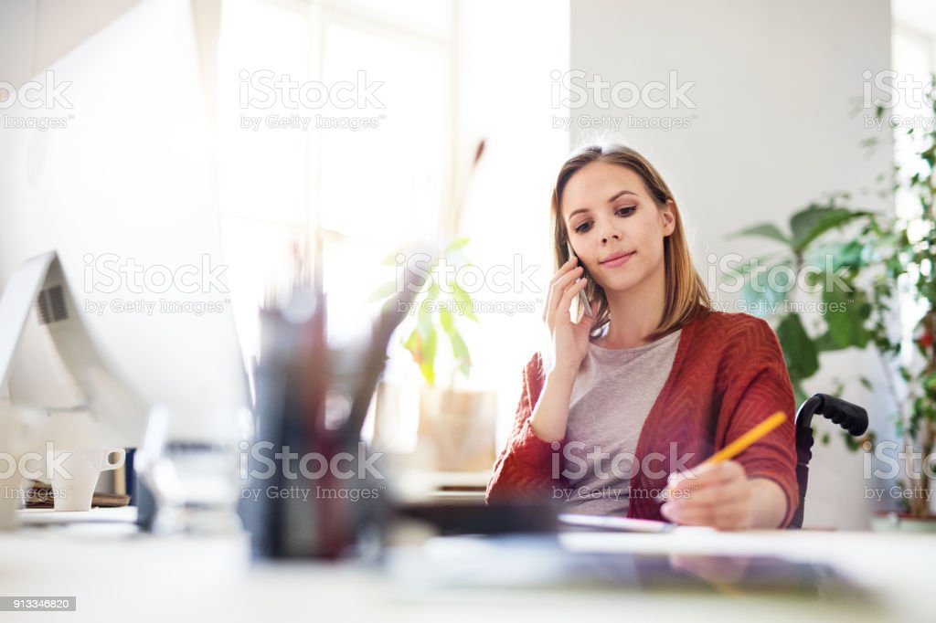 Businesswoman in wheelchair at the desk in her office. royalty-free stock photo