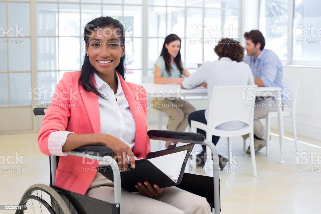 Geschäftsfrau im Rollstuhl hält Ordner und lächelt in die Kamera – Foto