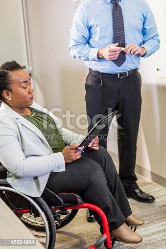 istock Businesswoman in wheelchair reading digital tablet 1145864934