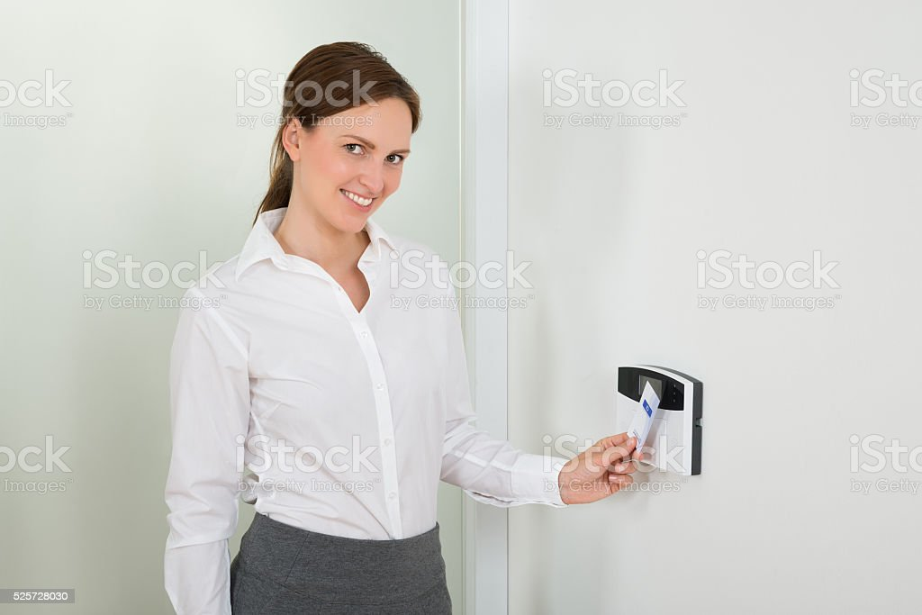 Businesswoman Inserting Keycard In Security System stock photo