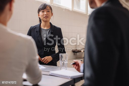 istock Businesswoman interacting with colleagues during presentation 610747072