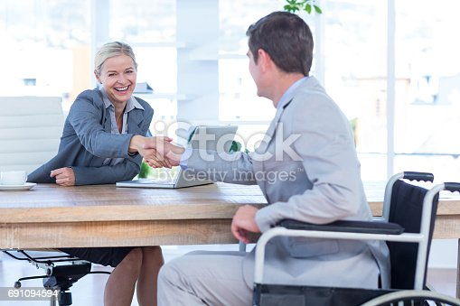 660681964istockphoto Businesswoman interviewing disabled job candidate 691094594