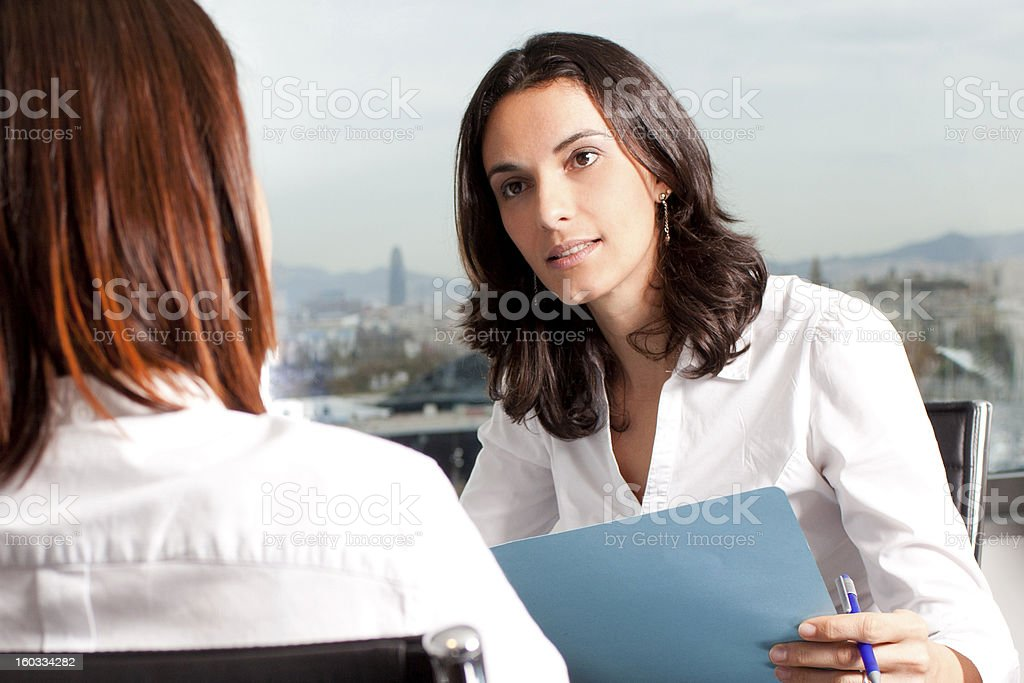 Businesswoman interviewing female intern holding blue paper stock photo