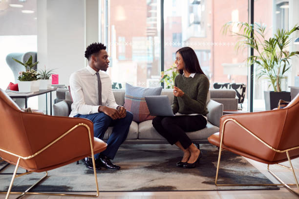 Businesswoman Interviewing Male Job Candidate In Seating Area Of Modern Office Businesswoman Interviewing Male Job Candidate In Seating Area Of Modern Office job interview stock pictures, royalty-free photos & images