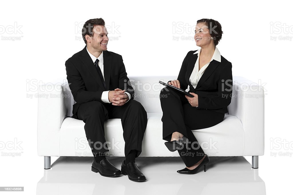 Businesswoman interviewing man on a couch royalty-free stock photo