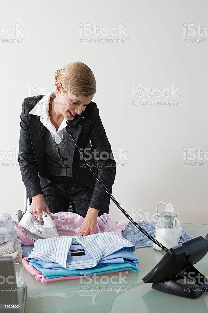 Businesswoman ironing at desk 免版稅 stock photo