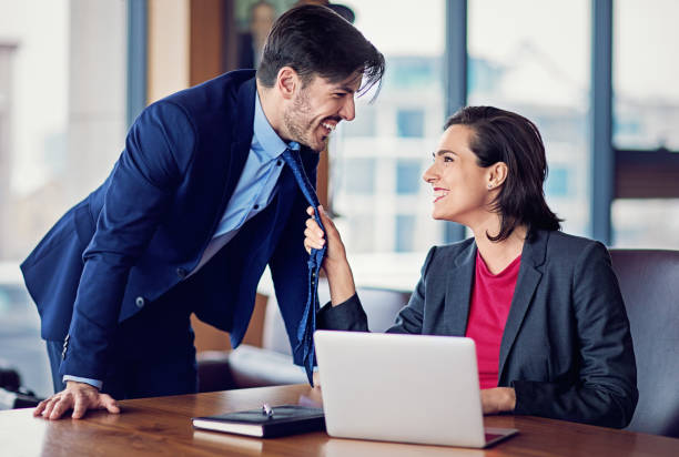 Businesswoman is flirting with her coworker in the office stock photo