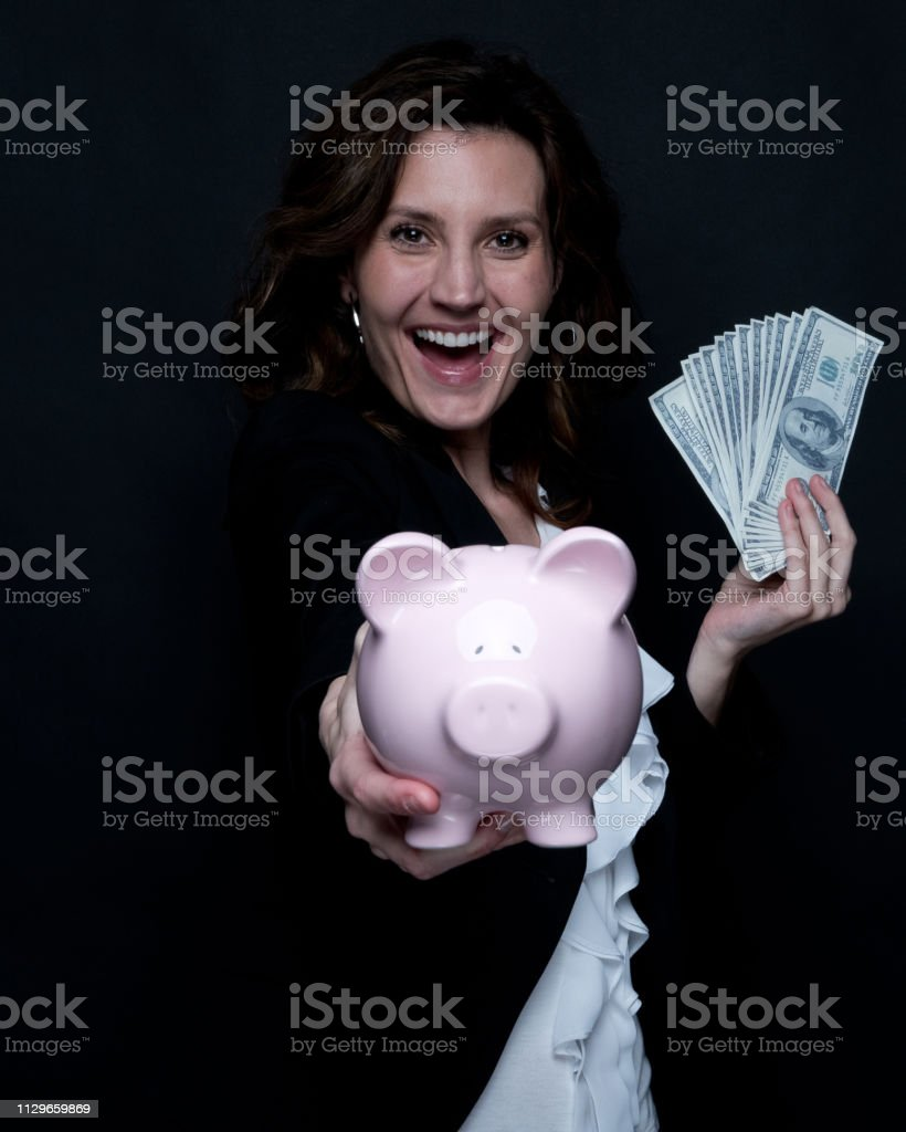 Businesswoman is holding a piggy bank and money stock photo