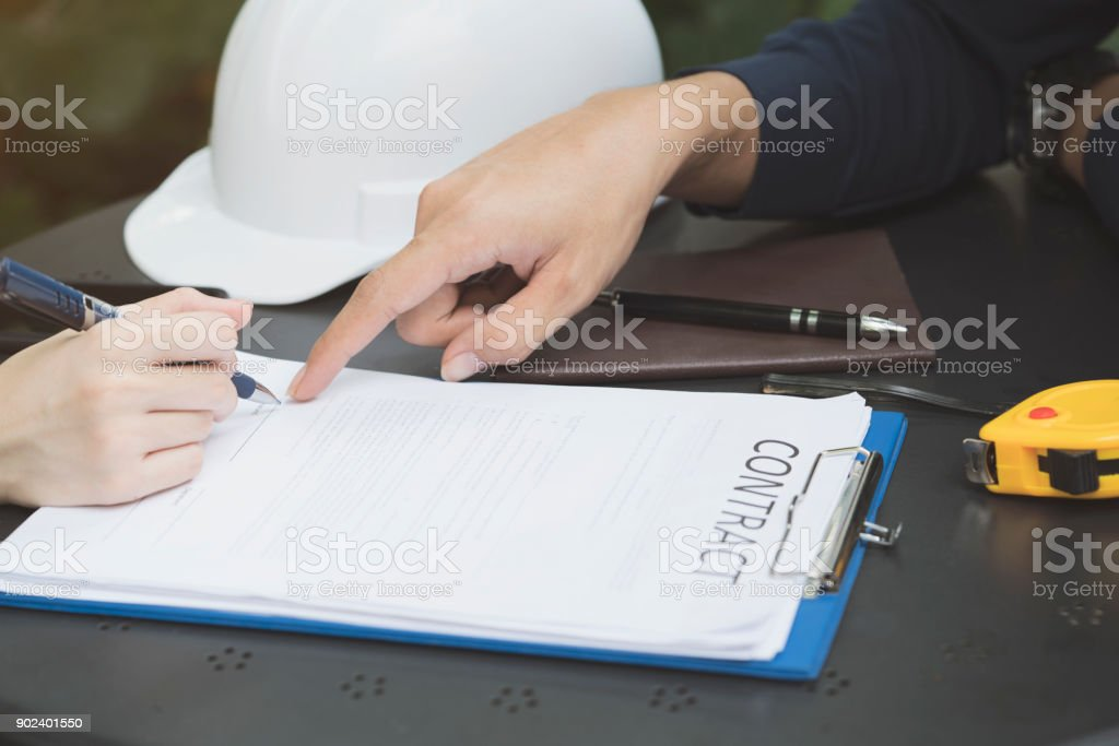 A businesswoman is negotiating a business deal or contracting and signing a contract, business negotiation concept stock photo