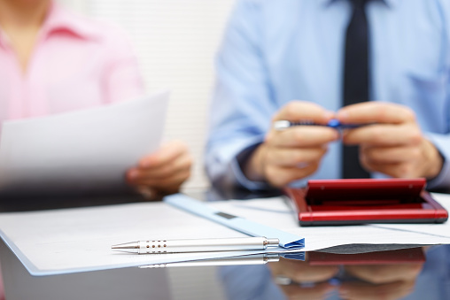 istock businesswoman is reading contract to businessman in blur background 469654664