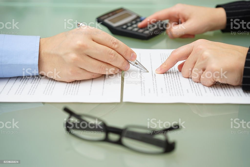 businesswoman is reviewing document with tax consultant and making calculations stock photo