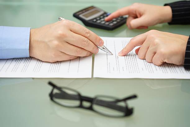 geschäftsfrau ist überprüfen dokument mit steuern-berater und rechen - rechtsassistent stock-fotos und bilder