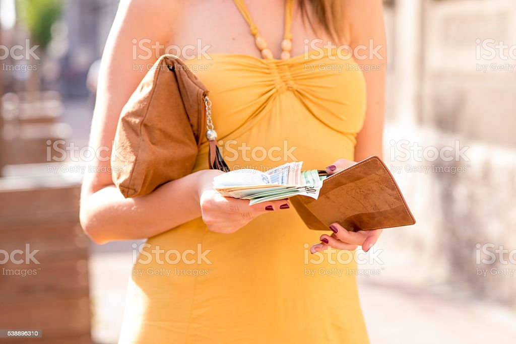 Businesswoman is taking out money from wallet stock photo
