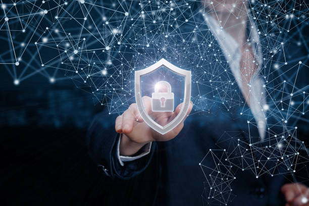 A businesswoman is touching a padlock inside a shield. A businesswoman is touching a padlock inside a shield surrounded with digital system of wireless connections at dark blurred background. threats stock pictures, royalty-free photos & images
