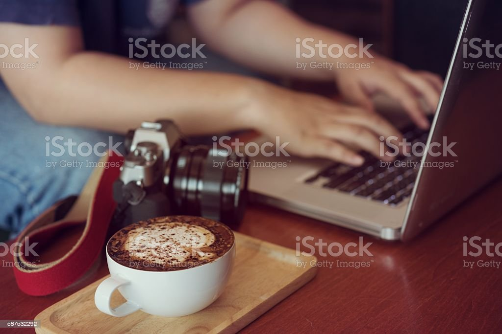 Businesswoman is working with laptop, holding a coffee in coffe stock photo