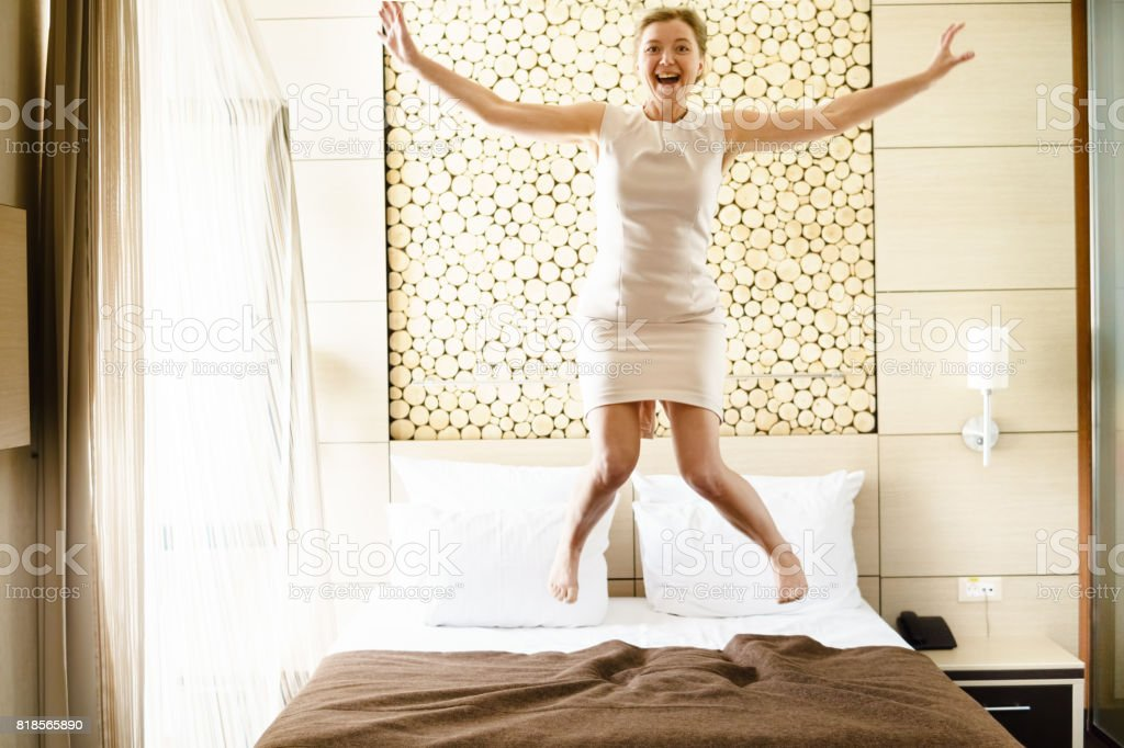 Businesswoman jumping on bed. stock photo