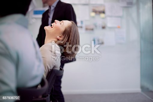 istock Businesswoman laughing reaction in office team meeting 637936702