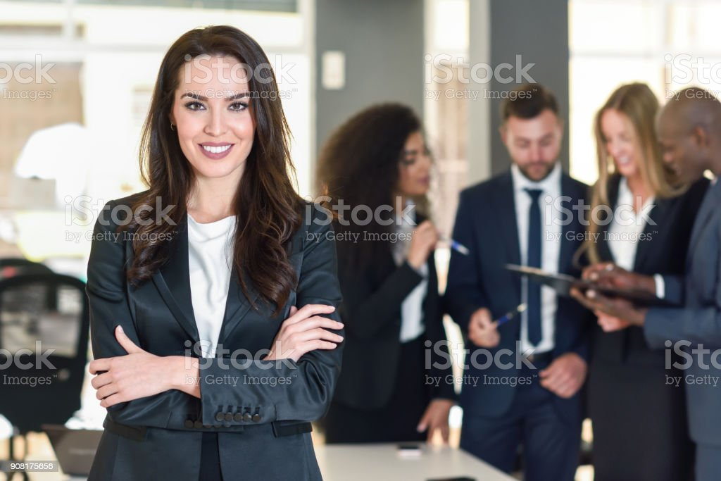 Businesswoman leader in modern office with businesspeople working at background stock photo