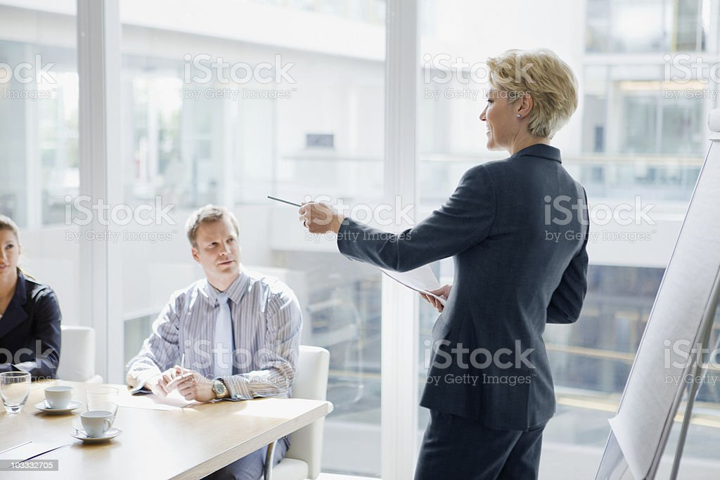Businesswoman leading discussion in meeting stock photo